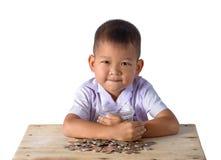 Милый мальчик азиатской страны имеет потеху с монетками в стеклянном шаре изолированном на белой предпосылке стоковое изображение