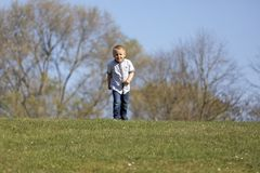 Милый мальчик бежать через усмехаться und травы стоковое изображение rf