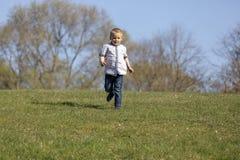 Милый мальчик бежать через усмехаться und травы стоковое фото rf