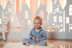 Милый мальчик белокурых волос в sleepwear около домов бумаги игрушки рождества Стоковая Фотография
