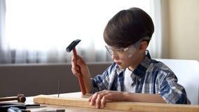 Милый мальчик бить молотком ноготь молотком в деревянной планке, хобби и часах досуга, мастерской стоковая фотография