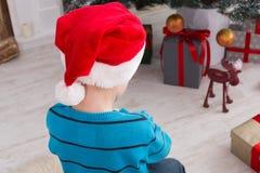Милый мальчик в шляпе santa развертывая подарки на рождество Стоковая Фотография RF