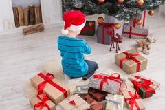 Милый мальчик в шляпе santa развертывая подарки на рождество Стоковые Изображения RF