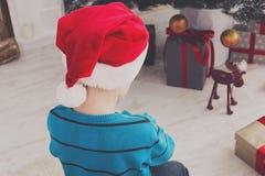 Милый мальчик в шляпе santa развертывая подарки на рождество Стоковое Изображение