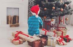 Милый мальчик в шляпе santa развертывая подарки на рождество Стоковое Изображение RF