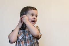 Милый мальчик говоря мобильным телефоном на светлой предпосылке Счастливое положение мальчика и говорить на смартфоне дома стоковые изображения rf