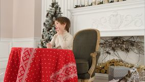 Милый мальчик думая что написать в его письме к Санта Клаусу Стоковое Изображение RF