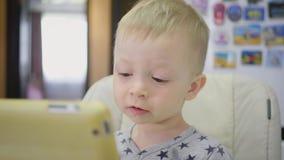 Милый мальчик, есть кашу на завтрак дома, пока наблюдающ мультфильм на планшете Дети и технология или сток-видео