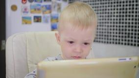 Милый мальчик, есть кашу на завтрак дома, пока наблюдающ мультфильм на планшете Дети и технология или акции видеоматериалы