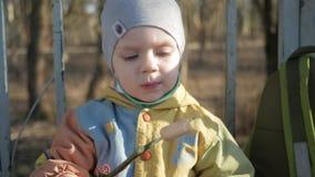 Милый мальчик ест сосиску снаружи Сваренный на bbq огня акции видеоматериалы