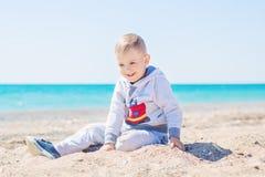 Милый мальчик играет в песке стоковое изображение