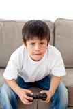 Милый мальчик играя видеоигры сидя на софе Стоковое Изображение RF