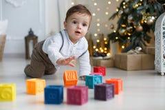 Милый мальчик играя около рождественской елки с покрашенными кубами Стоковое Изображение RF