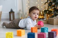 Милый мальчик играя около рождественской елки с покрашенными кубами Стоковая Фотография