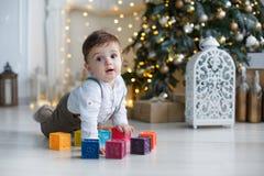 Милый мальчик играя около рождественской елки с покрашенными кубами Стоковая Фотография RF