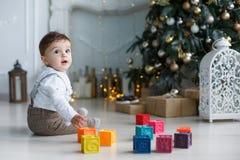 Милый мальчик играя около рождественской елки с покрашенными кубами Стоковое Изображение