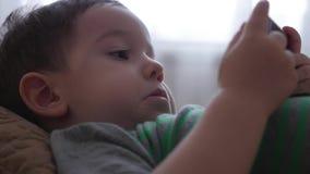 Милый мальчик играя по телефону, лежащ на его софе, играя с планшетом видеоматериал