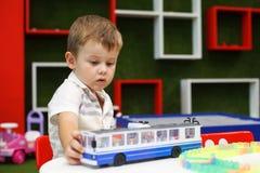 Милый мальчик играя с автомобилем вагонетки Превращаясь игрушки стоковые изображения