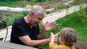 Милый мальчик играя с его дедом, outdoors лета акции видеоматериалы
