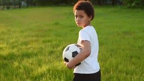 Милый мальчик играя футбол с шариком футбола на заходе солнца в парке S