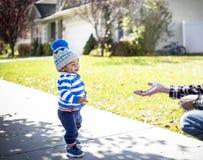 Милый мальчик идя на тротуар достигая для свободного выдаваемого стоковое фото rf