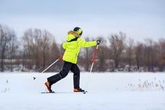 Милый мальчик имея потеху во время катания на лыжах на кресте стоковое изображение