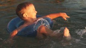 Милый мальчик имея потеху в море на заходе солнца движение медленное сток-видео