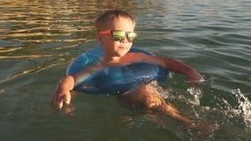 Милый мальчик имея потеху в море на заходе солнца движение медленное акции видеоматериалы
