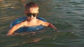 Милый мальчик имея потеху в море на заходе солнца движение медленное видеоматериал