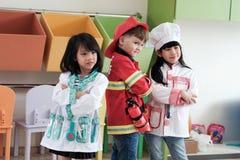 Милый мальчик и девушки играя как occupatio пожарного, доктора и кашевара Стоковое Изображение