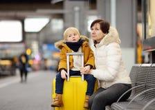 Милый мальчик и его экспресс бабушки/матери ждать на платформе железнодорожного вокзала Стоковые Фотографии RF