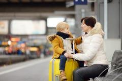 Милый мальчик и его экспресс бабушки/матери ждать на платформе железнодорожного вокзала Стоковое фото RF