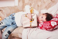 Милый мальчик лежит на софе с подарком в его руках Парень с стильной iroquois стрижкой и в ультрамодных современных одеждах Стоковые Изображения RF