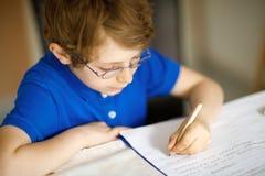 Милый мальчик маленького ребенка при стекла дома делая домашнюю работу, писать письма с красочными ручками стоковые изображения