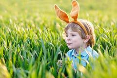 Милый мальчик маленького ребенка при уши зайчика имея потеху с традиционными пасхальными яйцами охотится на теплый солнечный день стоковые фотографии rf
