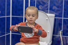 Милый мальчик малыша с smartphone в ванной комнате Мальчик сидя на туалете в ванной комнате дома с использованием a Стоковое фото RF