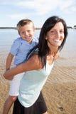 Милый мальчик матери и сына имея потеху отдыхая на пляже Стоковые Изображения RF