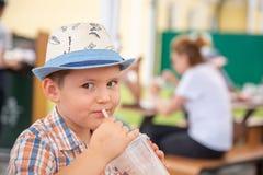Милый мальчик наслаждаясь молочным коктейлем во время тропических каникул стоковые изображения rf