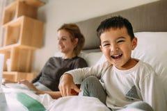 Милый мальчик на кровати с матерью на задней части стоковое фото rf