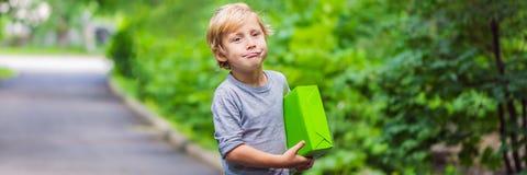 Милый мальчик носит подарочную коробку Дайте подарки и ЗНАМЯ концепции доставки, ДЛИННЫЙ ФОРМАТ стоковые фото