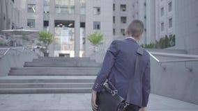Милый мальчик нося деловой костюм со случаем идя в город Ребенок как взрослый видеоматериал