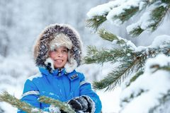 Милый мальчик нося теплые одежды играя на лесе зимы стоковые изображения rf