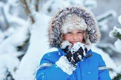 Милый мальчик нося теплые одежды играя на лесе зимы стоковые фото