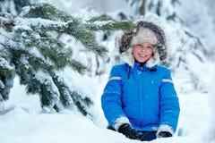 Милый мальчик нося теплые одежды играя на лесе зимы стоковое изображение