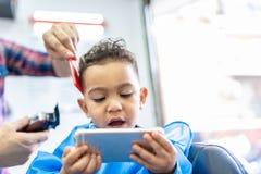 Милый мальчик получая отрезок волос в парикмахерской r стоковая фотография