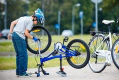 Милый мальчик ремонтируя его велосипед outdoors стоковое фото