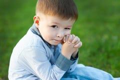 Милый мальчик сидит на зеленой траве Он ждет Концепция детей счастливых стоковое фото