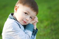 Милый мальчик сидит на зеленой траве Он ждет Концепция детей счастливых стоковое изображение