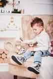Милый мальчик сидит на софе и смотрит старый золотой телефон Парень с стильной iroquois стрижкой и в ультрамодном mod Стоковое Изображение