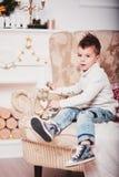 Милый мальчик сидит на софе и смотрит старый золотой телефон Парень с стильной iroquois стрижкой и в ультрамодном mod Стоковое Изображение RF